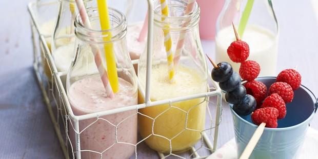 Strawberry and vanilla milkshakes in milk bottles with straws and berries