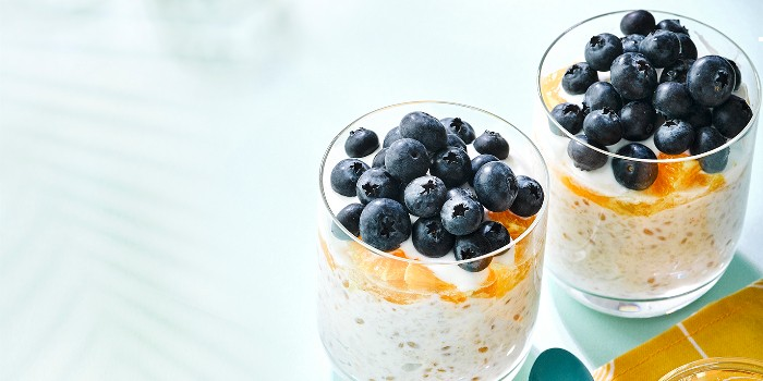 A glass full of bircher muesli topped with blueberries