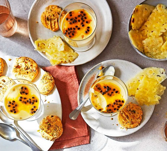 Three servings of passion fruit posset with pistachio-custard biscuits & fresh pineapple