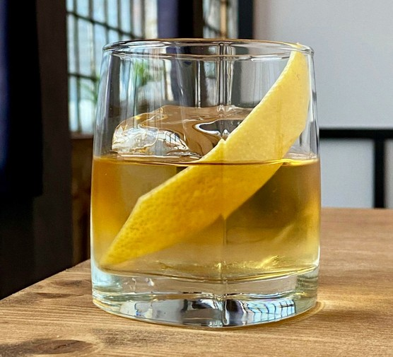 Iced coffee cocktail in glass with a citrus peel garnish