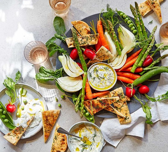 Summer vegetable & flatbread platter with dill & mustard dip spread out on a table