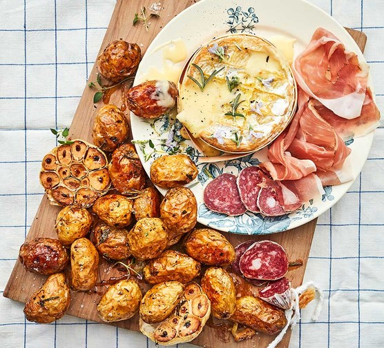 Baked cheese with roasted garlic Jersey Royals served on a platter