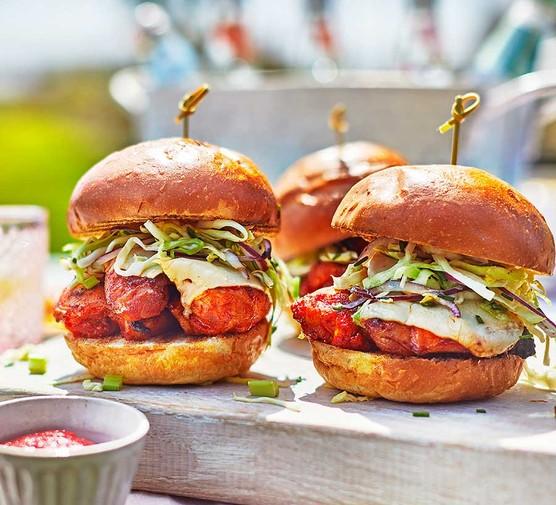 Three buffalo chicken burgers with ranch slaw on a board