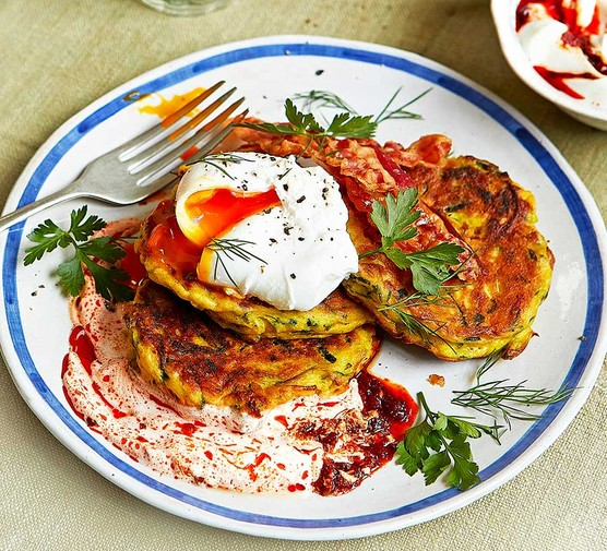 Courgette & ricotta fritters with poached eggs & harissa yogurt served on a plate