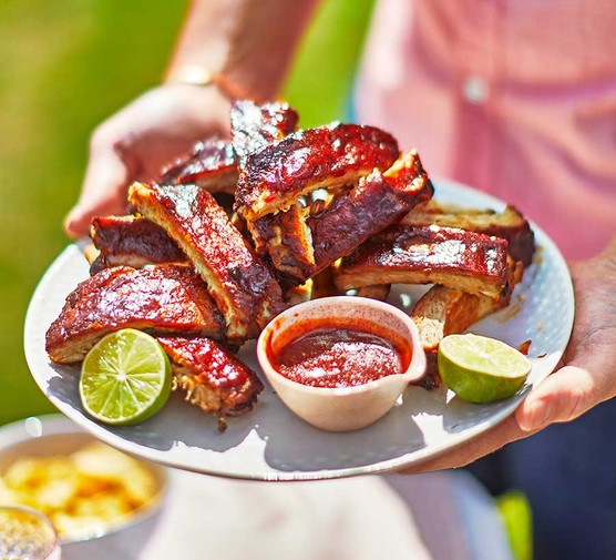 Fall-off-the-bone sticky barbecue ribs served on a platter with lime wedges