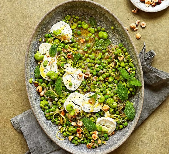 Lemony broad beans with goat's cheese, peas & mint in a large dish
