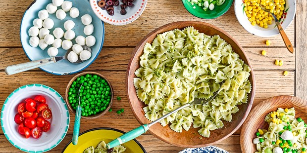 Selection of bowls with pesto pasta and toppings