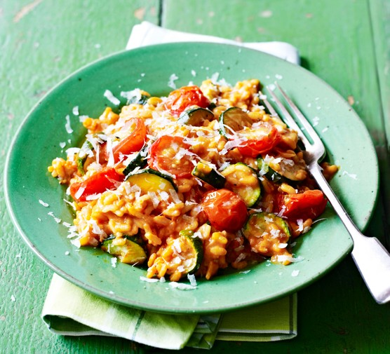 Tomato and courgette risotto in a green bowl, with fork