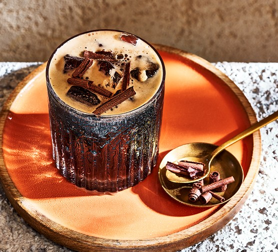 Boozy dark delight cocktail served in a short glass with chocolate shavings on top
