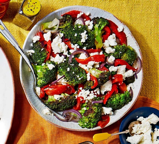 Broccoli with charred red peppers & feta served in a small bowl