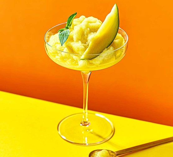 Frozen mango daiquiri served in a cocktail glass with a wedge of mango