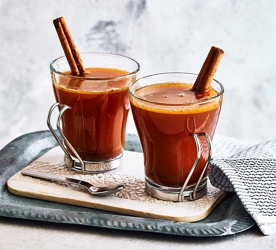Hot buttered rum in two glasses with cinnamon sticks