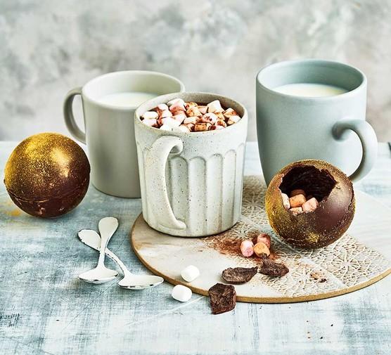 Hot chocolate bombs with 3 mugs alongside