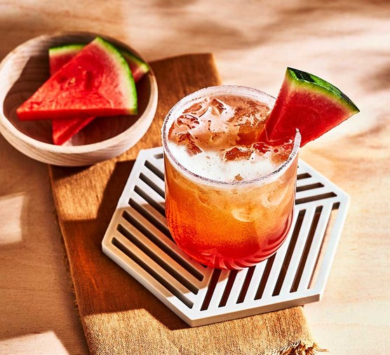 Tropical beer cocktail in a glass with a watermelon garnish
