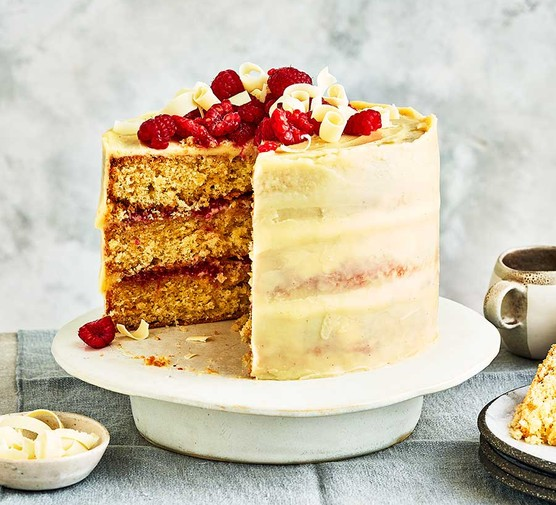 White chocolate layer cake, topped with raspberries, on a cake stand