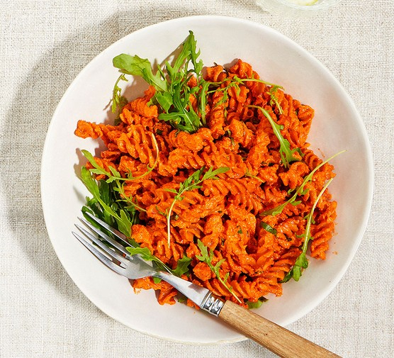 A bowl of red lentil pasta with creamy tomato & pepper sauce