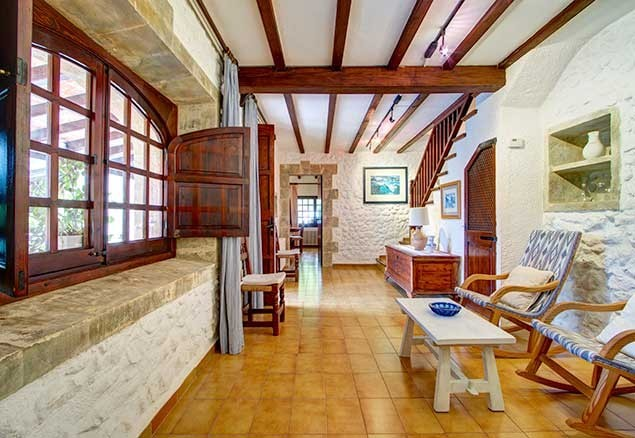 The villa is decorated in authentic Mallorcan style, with whitewashed walls, tiled floors and wooden furniture and beams