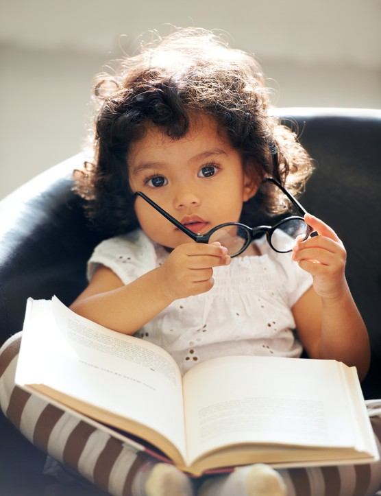A cute little girl holding glasses with a book on her lap