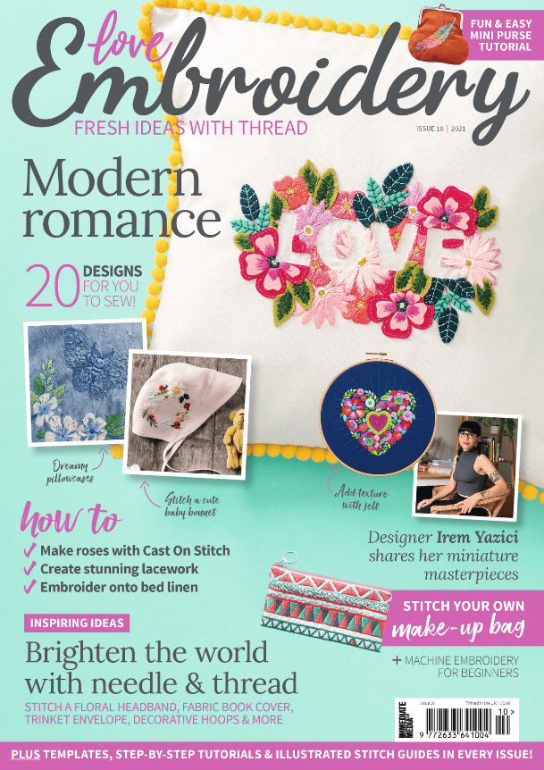 Love Embroidery issue 10 cover. The cover has a floral cushion depicting the word love on it and has a pom-pom trim, a ladybird baby bonnet, a line art moth, a colourful felt and stitched floral heart hoop, a geometric make-up pouch and a picture of designer Irem Yazici who sits with her desk behind her and is facing the camera and smiling.