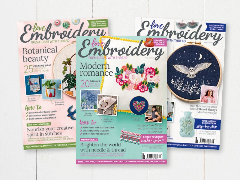 Three covers of Love Embroidery Magazine spread across a white wood background. The covers feature various embroidery projects.