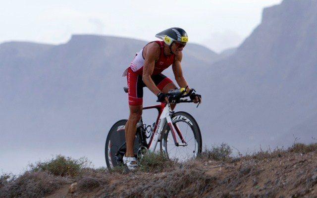 Triathlete climbing on the bike