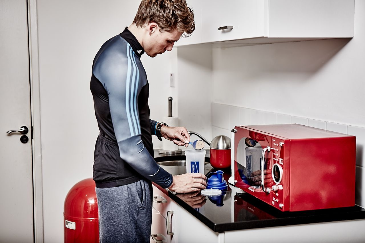 Triathlete making a recovery drink
