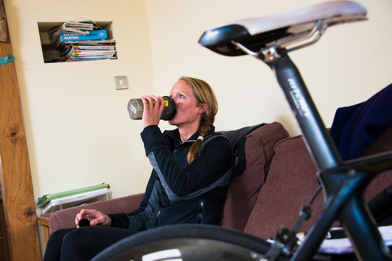 Female triathlete consuming a recovery drink