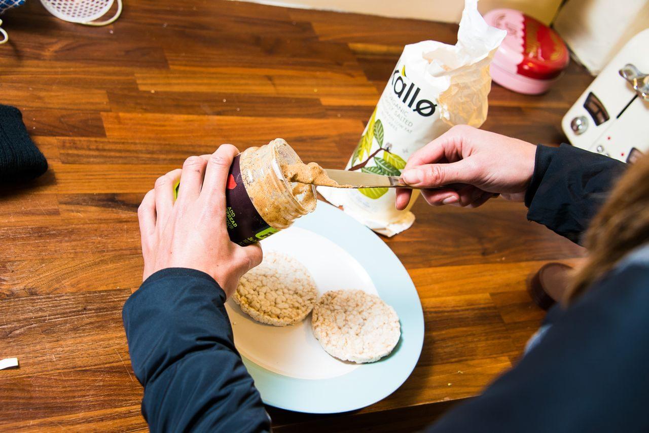 Female triathlete eating peanut butter on oat cakes