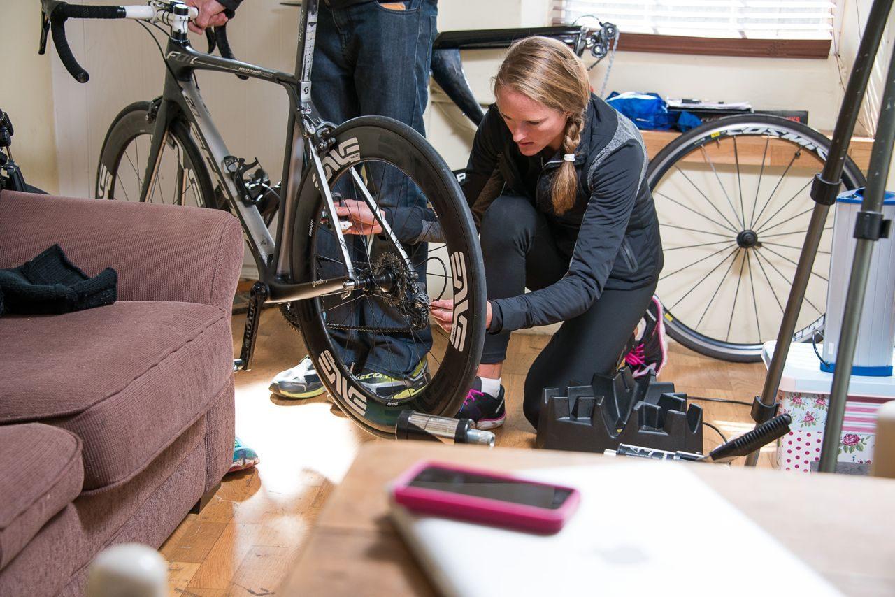 Female triathlete fine-tuning her road bike