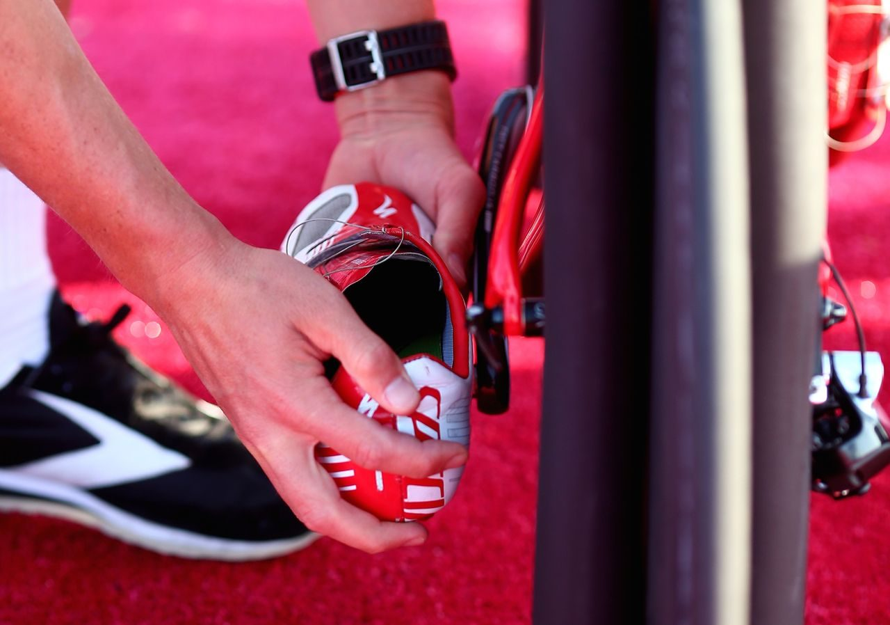 Triathlete prepping their bike shoes in transition