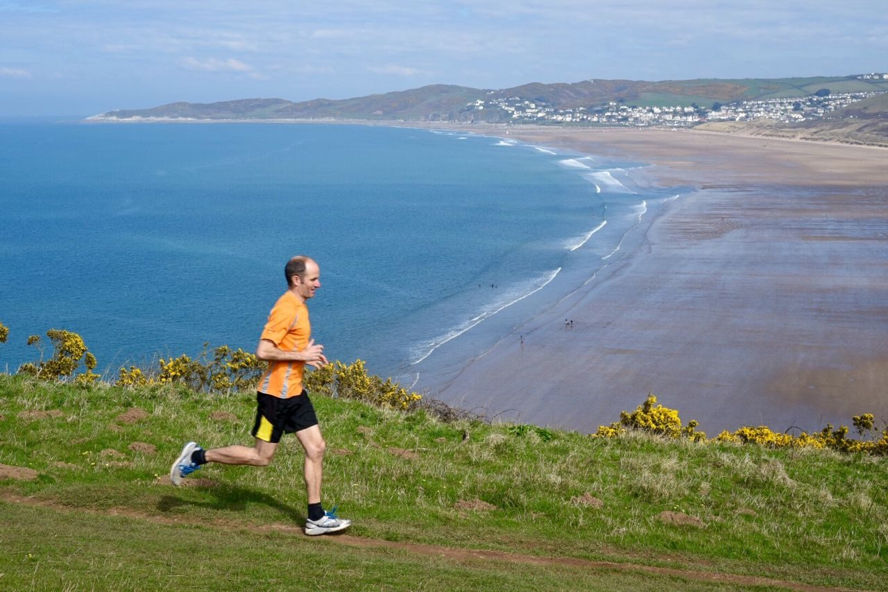 Triathlete running along a clifftop in Devon
