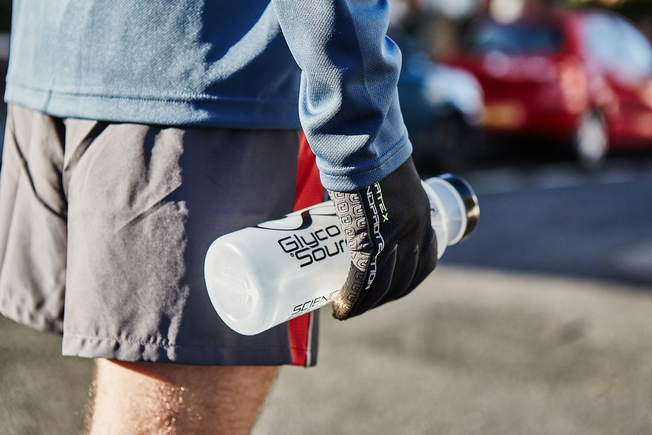 Triathlete in run training with an energy drink