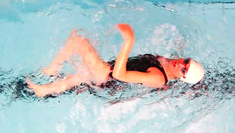 Female swimmer looking skyward while swimming