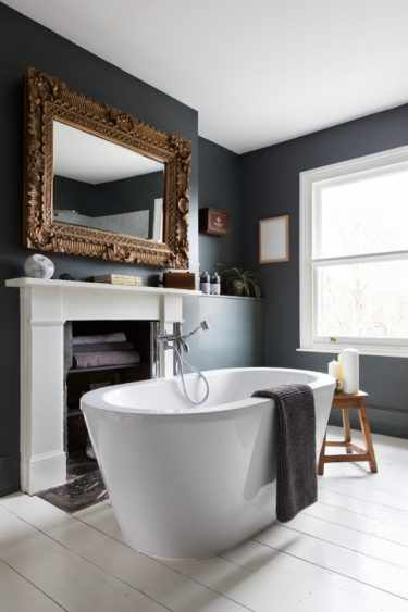Grand fireplace bathroom with freestanding bathtub and matt grey walls