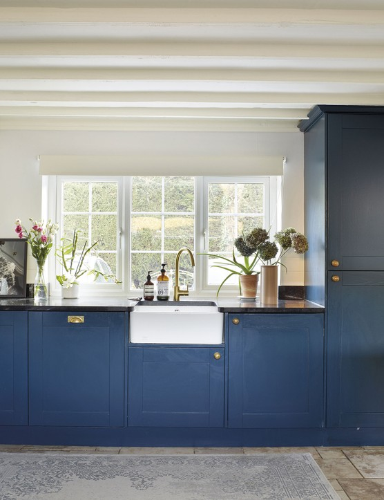 Brushed-brass handles and taps give a touch of luxury to the kitchen and stand out against the white tiles