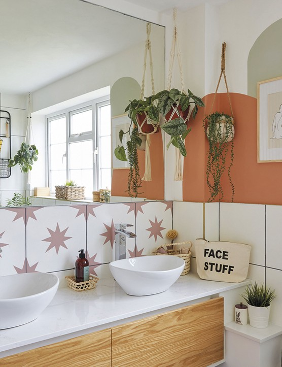 'The bathroom is a good size, but I wanted to make it feel more spacious, so I added the mirror and orange paint to add interest. The units were already there, and I painted the tiles. I'm really happy with them – they look like the real thing!'