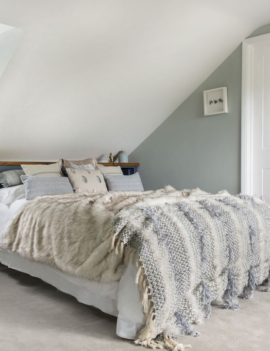 In the main bedroom in the loft, Charlie has painted the walls in a grey by Paint & Paper Library and, for a touch of fun, she's added some gold mouse lamps to the headboard, both by Graham & Green