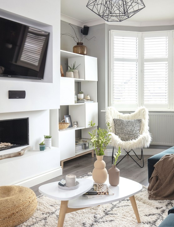 A large false wall houses the gas fire  and TV. The log-effect ties in well with  the nature-inspired accessories Yoko has used in the room, including a piece of driftwood she found on the beach