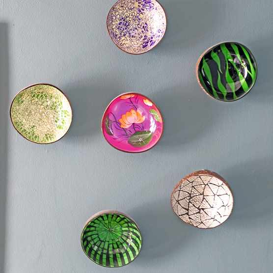 Colourful bowls, fixed to the wall with double-sided adhesive strips, make a bright 3D display against the blue wall.