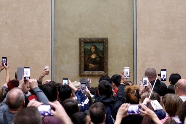 Visitors take pictures of the Mona Lisa by Leonardo Da Vinci, at the Louvre Museum in Paris © Pedro Fiúza/NurPhoto via Getty Images