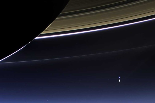 Earth (indicated by arrow) seen behind Saturn © NASA