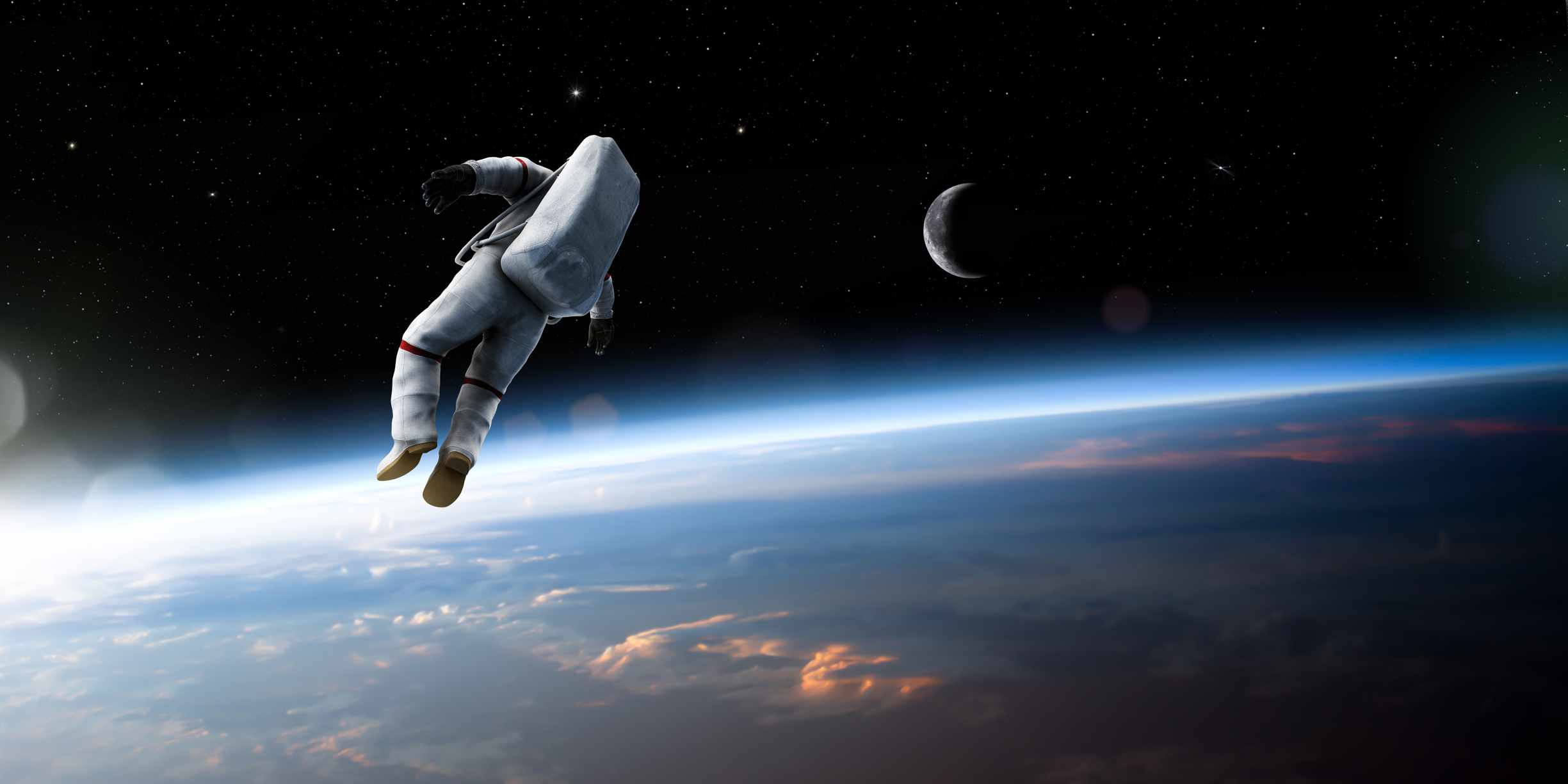 A composite image of an untethered astronaut in rear view, isolated and drifting off into deep space above the earth. This image uses a mixture of both CGI elements for the spaceman, and public domain NASA imagery for the earth and moon. The astronaut is wearing a generic space suit. © Getty Images