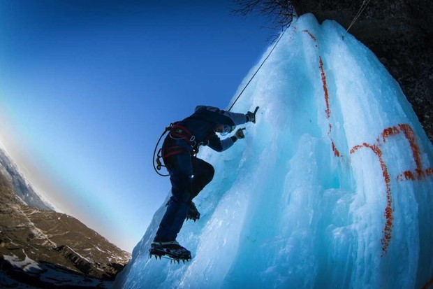 An ice climber ascends a frozen waterfall in Dagestan, Russia, during an ice climbing competition © Stanislav KrasilnikovTASS via Getty Images