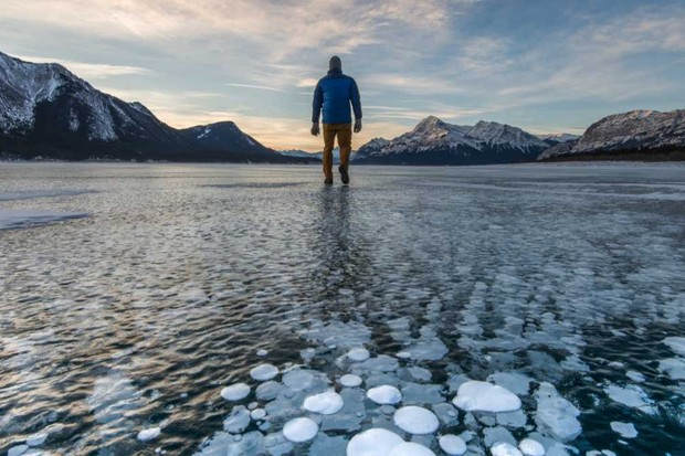 A man in Alberta, Canada, stands on frozen lake surface with bubbles of methane trapped in the ice © Ascent/PKS Media Inc/Getty Images