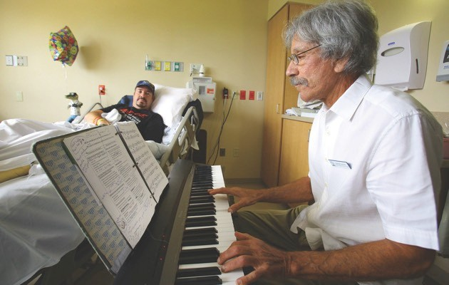 A music practitioner plays for a stroke patient at Florida Hospital Oceanside (© Press Association)