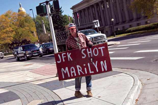 Conspiracy theorist displaying JFK sign on Denver street corner © Alamy