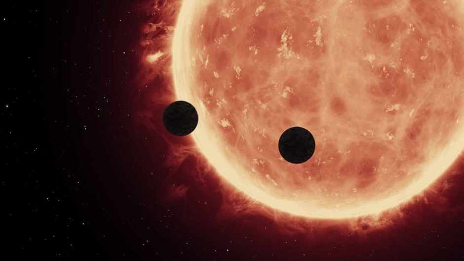 Artist's view of planets transiting a red dwarf star in the TRAPPIST-1 system © NASA, ESA, and STScI