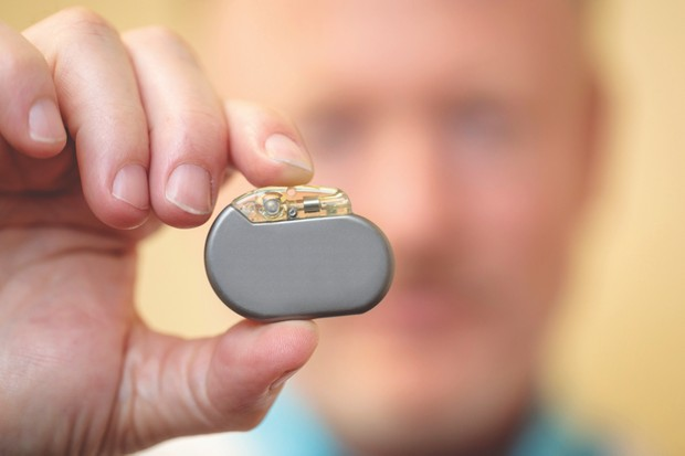 Charles Conway, MD, holds a vagus nerve stimulation device, which is implanted in research participants to treat depression on June 22, 2018. MATT MILLER/WASHINGTON UNIVERSITY SCHOOL OF MEDICINE