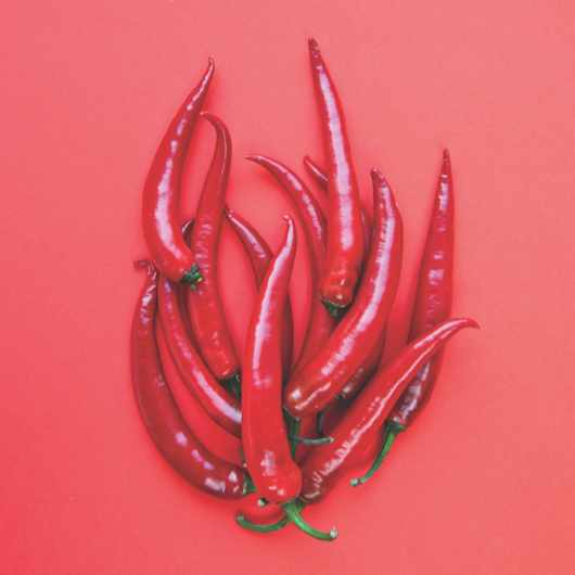 Red chill peppers arranged in the shape of a flame