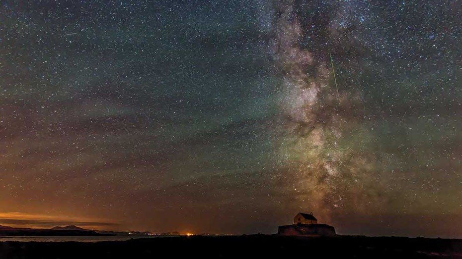 The Milky Way over St. Cwyfan Church on the island of Anglesey, with a Perseid in the frame © Kevin Lewis